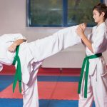 martial arts girl kicking boy in training class