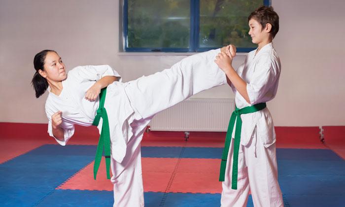 martial arts girl kicking boy in training class
