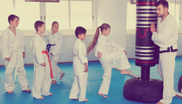 martial arts students take turns kicking