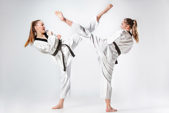 two teen girls martial arts students kicking
