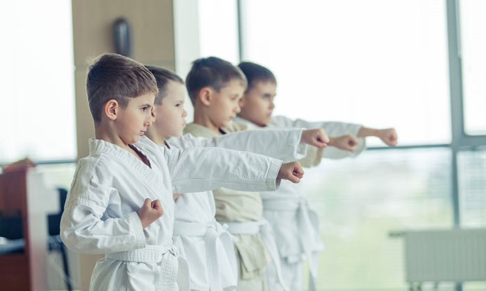 young boys in martial arts class practicing arm stretch
