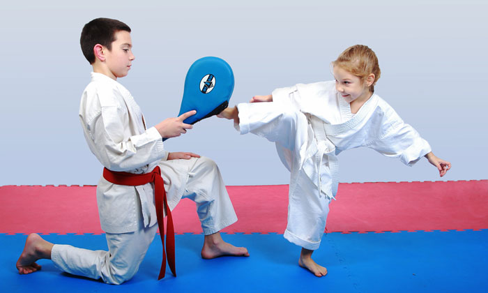 young girl kicking in martial arts class