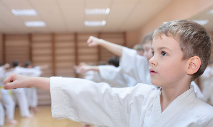 young martial arts boys in class with arms out