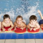 group of young swimmers in training with kickboards