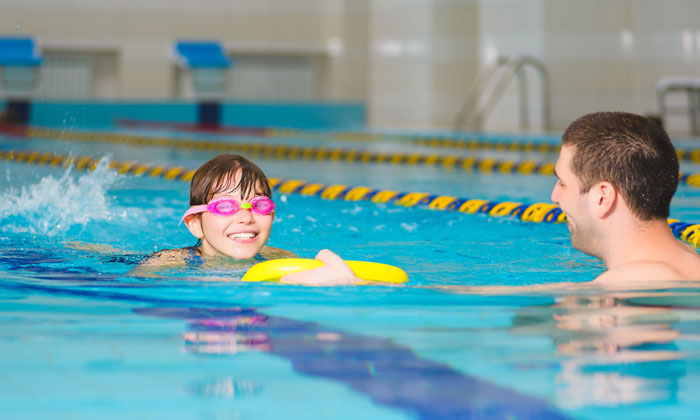 young goggle kid learning to swim with instructor